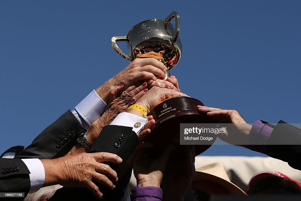 Part owners of Fiorente hold up the Melbourne Cup after winning race 7 The Emirates Melbourne Cup during Melbourne Cup Day at Flemington Racecourse on November 5, 2013 in Melbourne, Australia.