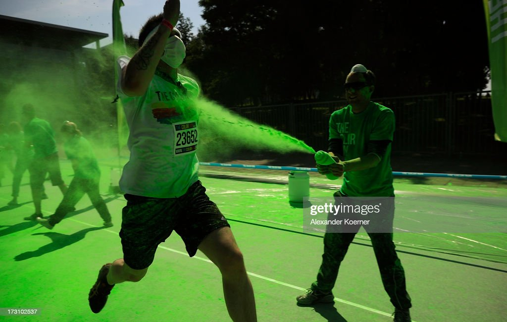A partcipiant is covered in green poder as he runs through the green colour zone during the Color Run at the Hanover Fairgrounds on July 7, 2013 in Hanover, Germany. The Color Run is a sponsored 5km run during which participants, who dress in white, have a different coloured corn-flour based powder thrown at them for every kilometer that they run. This was the second run to be held in Germany, attacting 5000 runners.