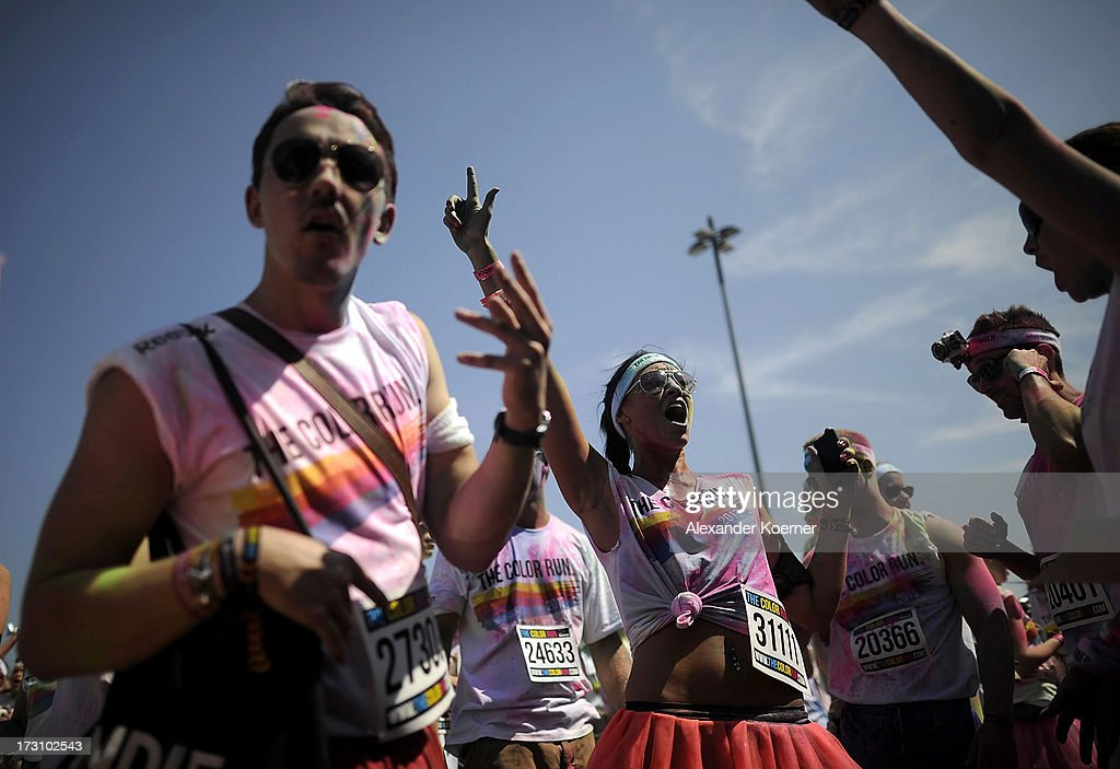Partcipiants celebrate during a party held after the Color Run at the Hanover Fairgrounds on July 7, 2013 in Hanover, Germany. The Color Run is a sponsored 5km run during which participants, who dress in white, have a different coloured corn-flour based powder thrown at them for every kilometer that they run. This was the second run to be held in Germany, attacting 5000 runners.