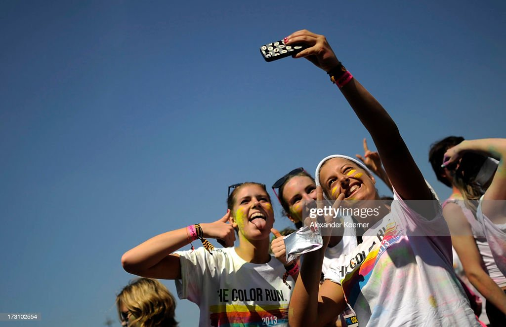 Partcipiants take a photo of themselves during a party held after the Color Run at the Hanover Fairgrounds on July 7, 2013 in Hanover, Germany. The Color Run is a sponsored 5km run during which participants, who dress in white, have a different coloured corn-flour based powder thrown at them for every kilometer that they run. This was the second run to be held in Germany, attacting 5000 runners.
