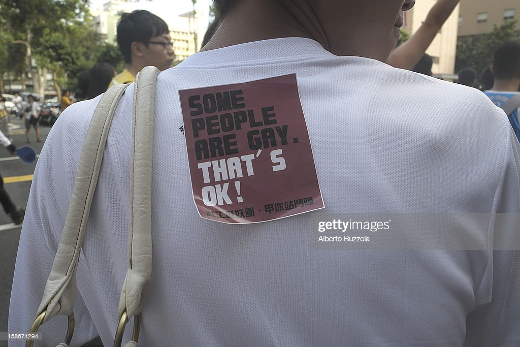 A partecipant of the Taipei Gay and Lesbian Pride Parade with a sticker stuck on his back that reads that to be gay is ok..