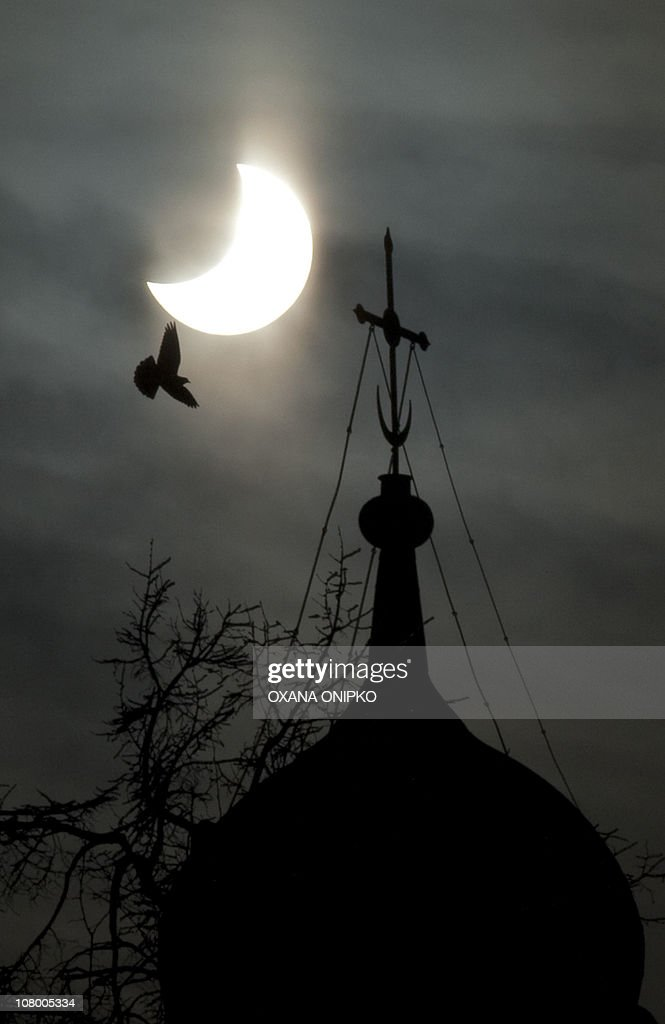 A partial solar eclipse of the sun is seen above a dome of the Lifegiving Trinity Russian Orthodox Cathedral in Moscow on January 4 2011 Europe was...
