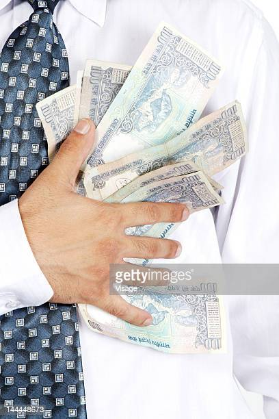 Partial view of a business man holding currency notes in his pockets