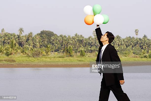 Partial view of a businessman holding balloons