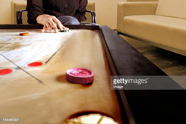Partial view of a hand ready to strike the queen coin on carrom board