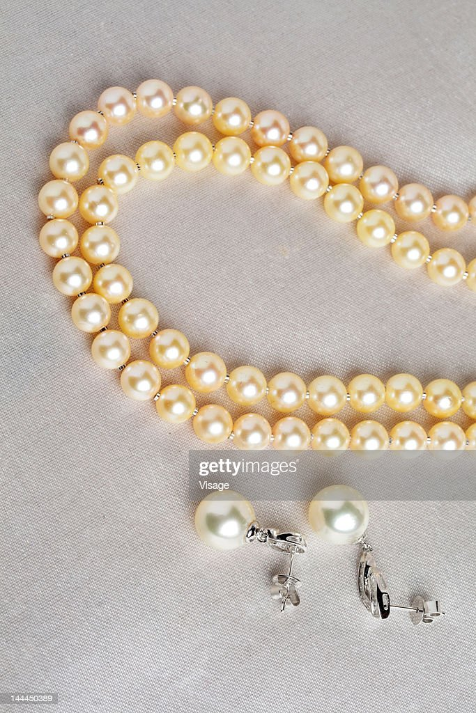 Partial view of a pearl necklace and earrings