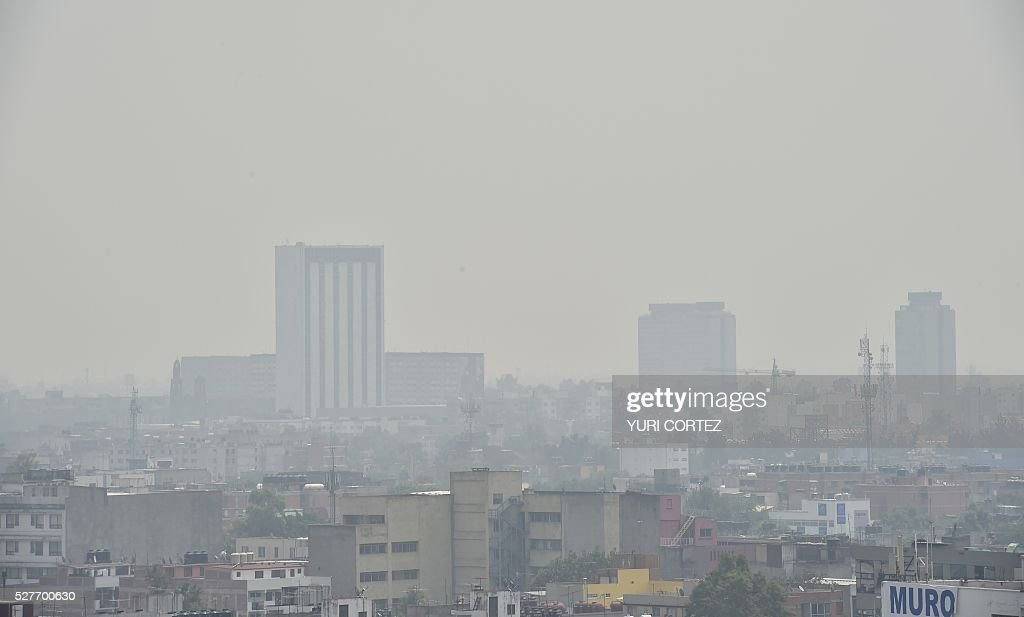 Partial view of Mexico City covered in smog on May 3, 2016. Mexico City officials issued a new air pollution alert yesterday, meaning that 40 percent of vehicles will be banned on Tuesday, while industries will be required to cut emissions. The alarm was raised after ozone levels reached 161 points, above the 150 level. The threshold was lowered from 190 to 150 last month. / AFP / YURI