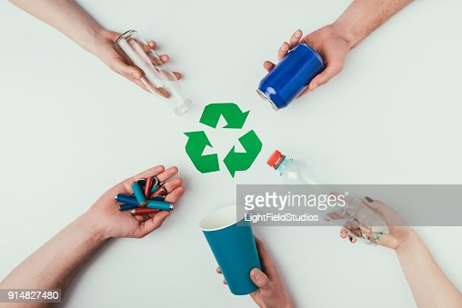 partial view of people showing various types of garbage around recycle sign isolated on grey : Stock Photo
