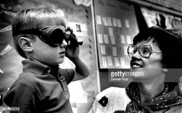 Partially blind teacher Marge West shows her first grade student Jason Hughes what her vision is like that of looking through a straw with a pair of...