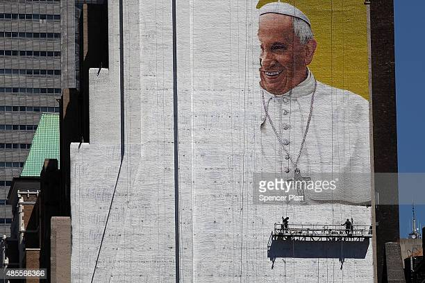 A partially completed mural of Pope Francis is viewed on the side of a building in midtown Manhattan on August 28 2015 in New York City The Pope will...