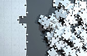 Partially assembled puzzle with white jigsaw pieces, while others are still messy and unordered. One side of the image shows part of a completed puzzle, while the other shows the work in progress on a