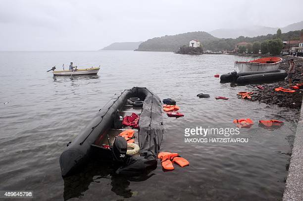A partially deflated boat and orange life vests float in the water off Sykamia beach west of the port of Mytilene on the Greek island of Lesbos after...