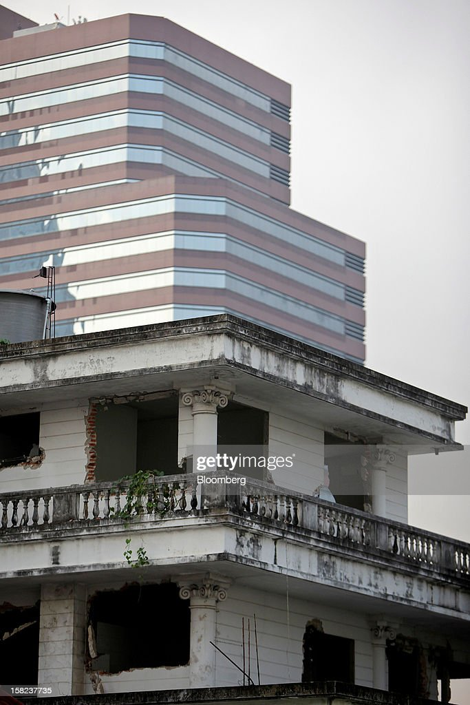 A partially demolished house stands in front of a commercial high rise building off Langsuan road in Bangkok, Thailand, on Tuesday, Dec. 11, 2012. The Crown Property Bureau owns about 41,300 rai (66 square kilometers) of land across the country, about a fifth of which is in Bangkok, according to Aviruth Wongbuddhapitak, an adviser to the CPB who sits on the board of two of its subsidiaries. Photographer: Dario Pignatelli/Bloomberg via Getty Images