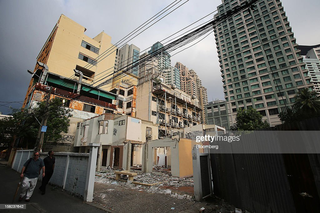 Partially demolished houses stand in a side street off Langsuan road as high rise buildings stand in the background in Bangkok, Thailand, on Tuesday, Dec. 11, 2012. The Crown Property Bureau owns about 41,300 rai (66 square kilometers) of land across the country, about a fifth of which is in Bangkok, according to Aviruth Wongbuddhapitak, an adviser to the CPB who sits on the board of two of its subsidiaries. Photographer: Dario Pignatelli/Bloomberg via Getty Images