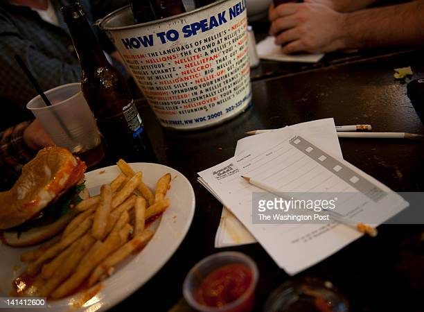 A partially eaten meal and paper for trivia sits on a table as friends enjoy an evening of trivia at the Nellie's Sports Bar in Washington DC on...