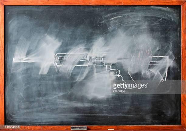 Partially erased chalk drawing of gun on blackboard