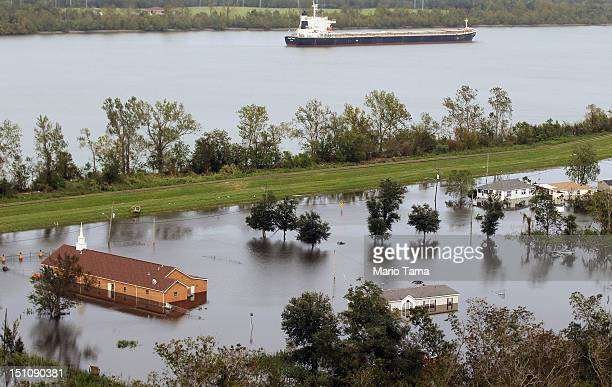 Partially submerged homes and a church sit in Hurricane Isaac's flood waters as a cargo ship passes on the Mississippi River on August 31 2012 in...