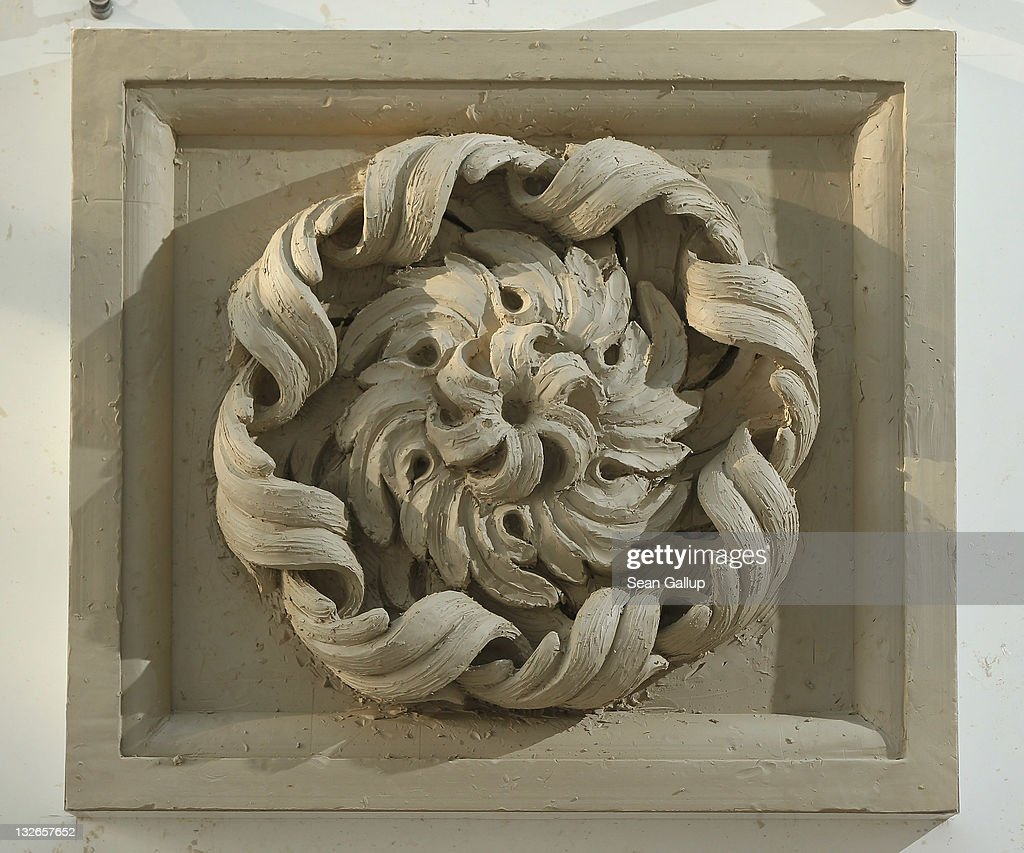 A partially-completed rosette made from clay stands on an easel at the Schlossbauhuette studio where a team of sculptors is creating decorative elements for the facade of the Berliner Schloss city palace on November 11, 2011 in Berlin, Germany. The Berliner Schloss was the residence of the Prussian Kaiser and was among the major architectural landmarks of Berlin until it was heavily damaged by Allied bombing in 1945. The communist authorities of East Berlin demolished the building in the 1950s, and today's Berlin government is pursuing an ambitious project to rebuild the palace according to a design by Italian architect Franco Stella, which will recreate the facade of the building but with a modern interior at a cost of approximately EUR 590 million. The Humboldt Forum, the foundation leading the project, has given the Schlossbauhuette sculptors the formidable task of recreating the hundreds of architectural elements that decorated the facade, and though some original pieces were saved, more often the sculptors have only old black and white photos as reference.