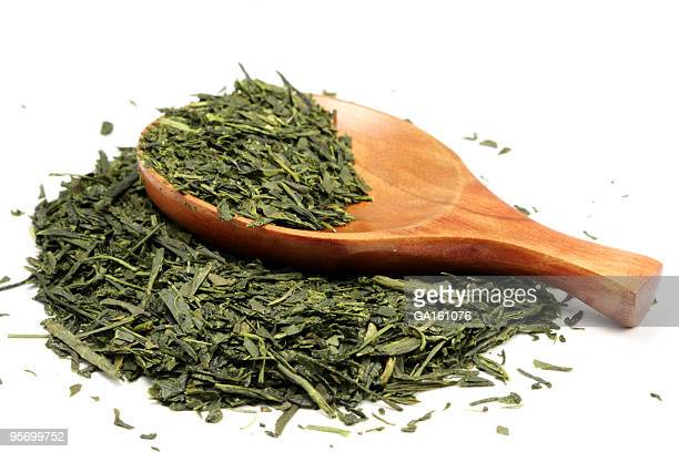 Partially-filled wooden spoon laying on loose green tea