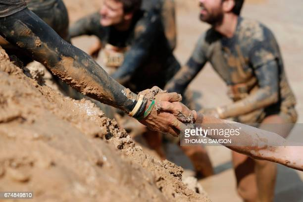 TOPSHOT A participant assists another up a hill during the Mud Day Paris 2017 obstacle course in Beynes on April 29 2017 / AFP PHOTO / THOMAS SAMSON