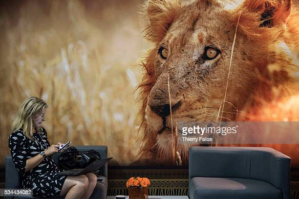 A participant at the World Economic Forum on Africa held in Kigali Rwanda in May 2016 consults her mobile phone under a poster of a male lion