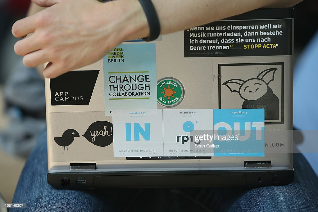 A participant clutches a laptop decorated with activists' stickers on the first day of the re:publica 2013 conferences on May 6, 2013 in Berlin, Germany. Re:publica, a three-day-event, brings together bloggers and digitial media professionals for a series of conferences on affecting social, political and economic change through the Internet.