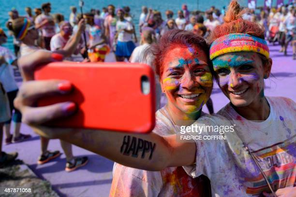Participant covered with coloured powders pose for a selfie during the Color Run on September 12 2015 in Lausanne The Color Run is a 5km run that...