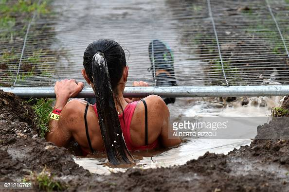 A participant crawl under a fence during the Legion Run a 5kilometer teamoriented run with obstacles of mud fire ice and barbed wire in Rome on...