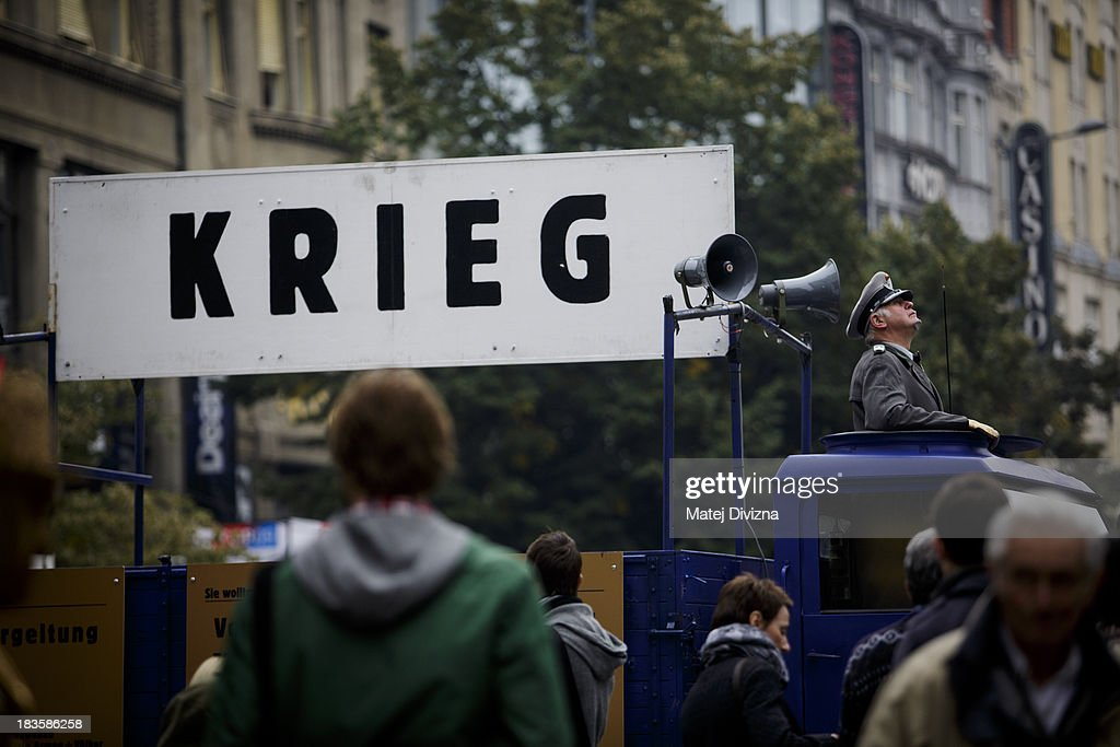 A participant dressed as a Nazi soldier stands on a vehicle during the 'Klassenkampf statt Weltkrieg' (Class Struggle Instead of World War), a campaign supported by Deutsche Kommunistische Partei (DKP), at the Wenceslas square on October 7, 2013 in Prague, Czech Republic. The meeting took place to mark the 75th Anniversary of The Munich Pact. A banner reads 'War' on the vehicle.