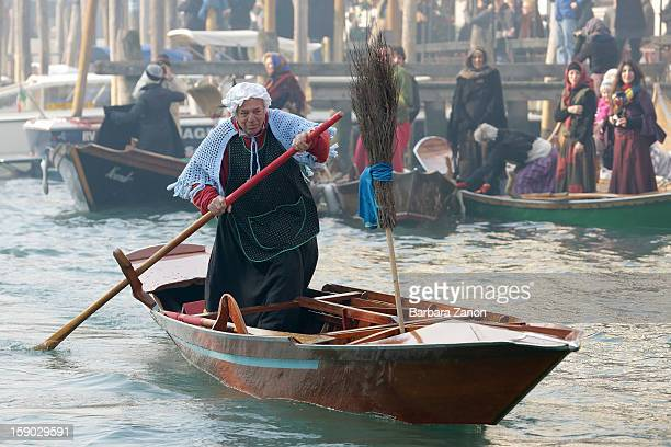A participant dressed as 'Befana' rows on Gran Canal during the traditional Epiphany Boat Race on January 6 2013 in Venice Italy In Italy Epiphany is...
