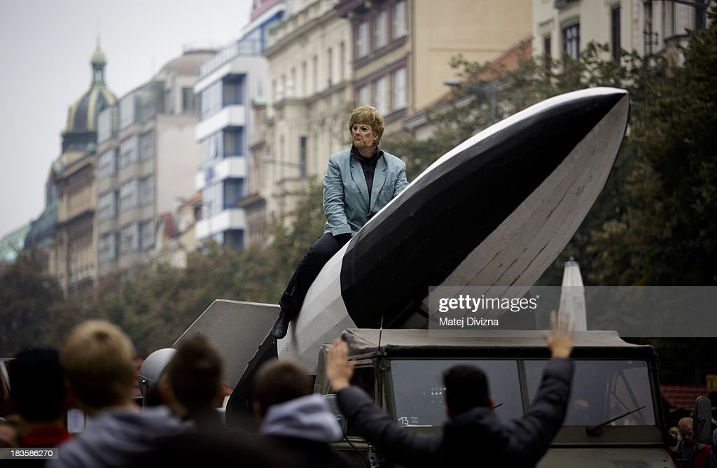 A participant dressed as German Chancellor Angela Merkel sits on a large rocket during the 'Klassenkampf statt Weltkrieg' (Class Struggle Instead of World War), a campaign supported by Deutsche Kommunistische Partei (DKP), at the Wenceslas square on October 7, 2013 in Prague, Czech Republic. The meeting took place to mark the 75th Anniversary of The Munich Pact.