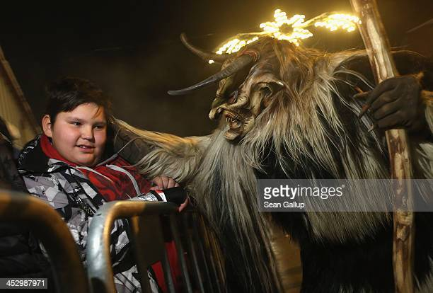 A participant dressed as the Krampus creature in search of delinquent children approaches a little boy during Krampus night on November 30 2013 in...