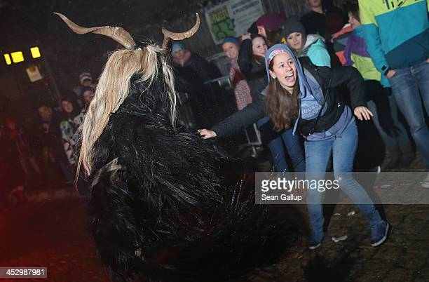 A participant dressed as the Krampus creature in search of delinquent children attempts to pull away a young girl from onlookers during Krampus night...