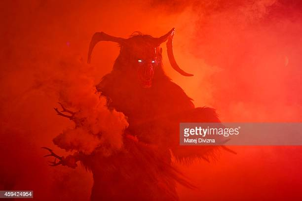 A participant dressed as the Krampus creature walks the streets during Krampus gathering on November 22 2014 in Schladming Austria Krampus is a...