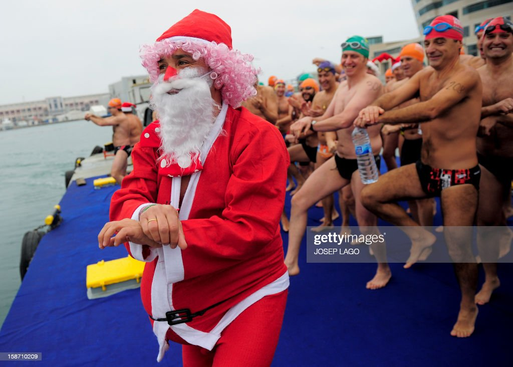 A participant dressed up as Santa Claus dances before taking part in the103rd edition of the Copa Nadal (Christmas Cup) at Barcelona's Port Vell on December 25, 2012. The traditional 200-meter Christmas swimming race gathered around 400 participants at the Old Harbour of Barcelona.