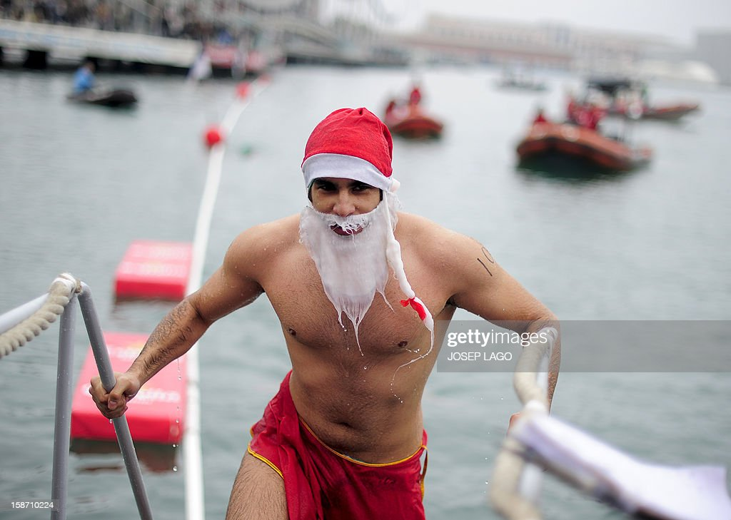 A participant dressed up as Santa Claus gets out of the water at Barcelona's Port Vell during the103rd edition of the Copa Nadal (Christmas Cup) on December 25, 2012. The traditional 200-meter Christmas swimming race gathered around 400 participants at the Old Harbour of Barcelona.