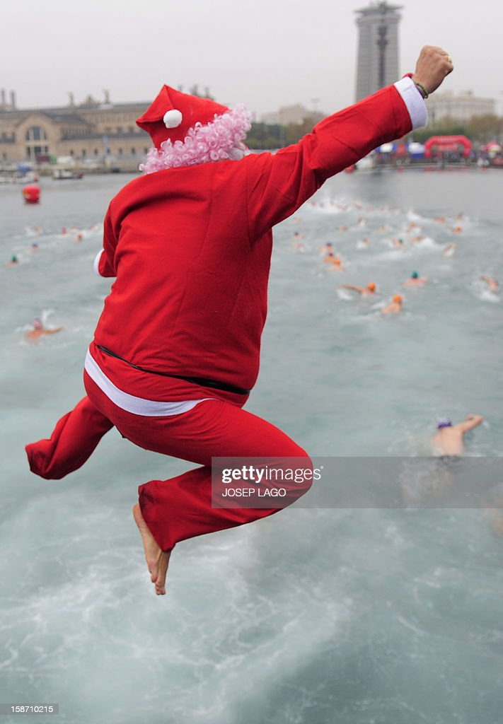 A participant dressed up as Santa Claus jumps in the cold water of Barcelona's Port Vell as he takes part in the103rd edition of the Copa Nadal (Christmas Cup) on December 25, 2012. The traditional 200-meter Christmas swimming race gathered around 400 participants at the Old Harbour of Barcelona.