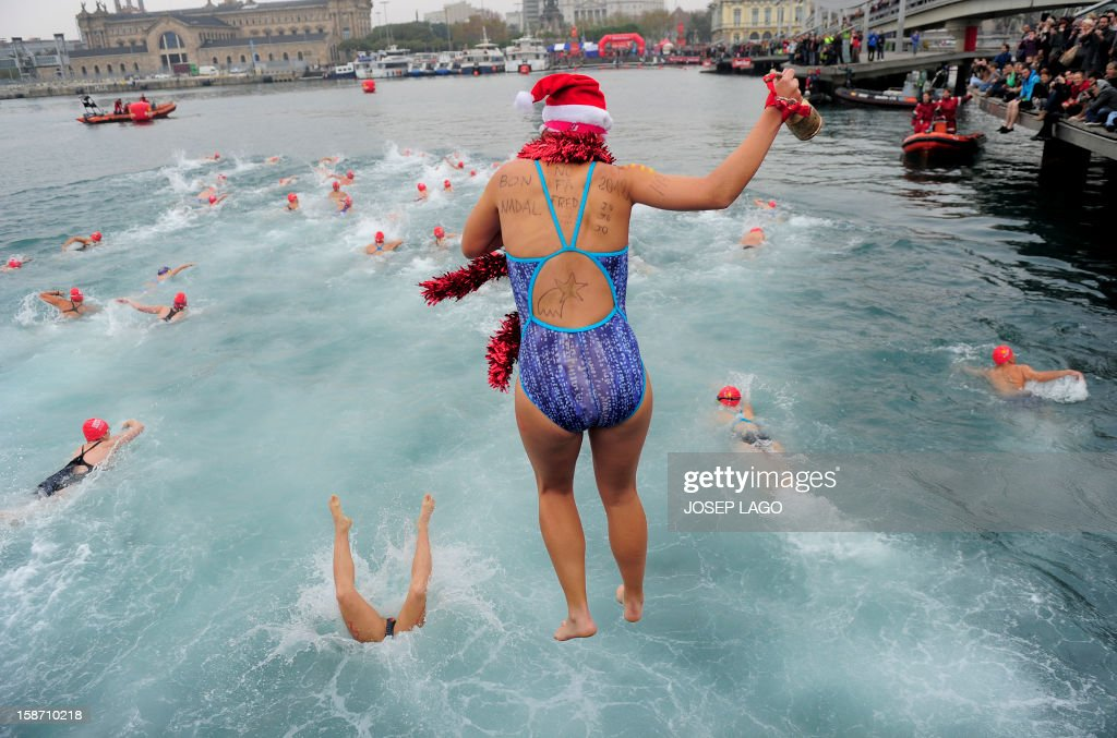 A participant dressed up as Santa Claus jumps in the cold water of Barcelona's Port Vell as she takes part in the103rd edition of the Copa Nadal (Christmas Cup) on December 25, 2012. The traditional 200-meter Christmas swimming race gathered around 400 participants at the Old Harbour of Barcelona.