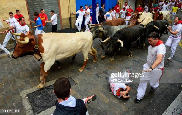 A participant falls as others run ahead of Miura's fighting bulls during the eighth and last bull run of the San Fermin festival in Pamplona northern...