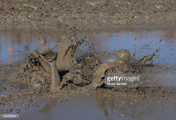 A participant falls during the Mud Mile obstacle in the Tough Mudder event at Raceway Park on October 20 2012 in Englishtown New Jersey