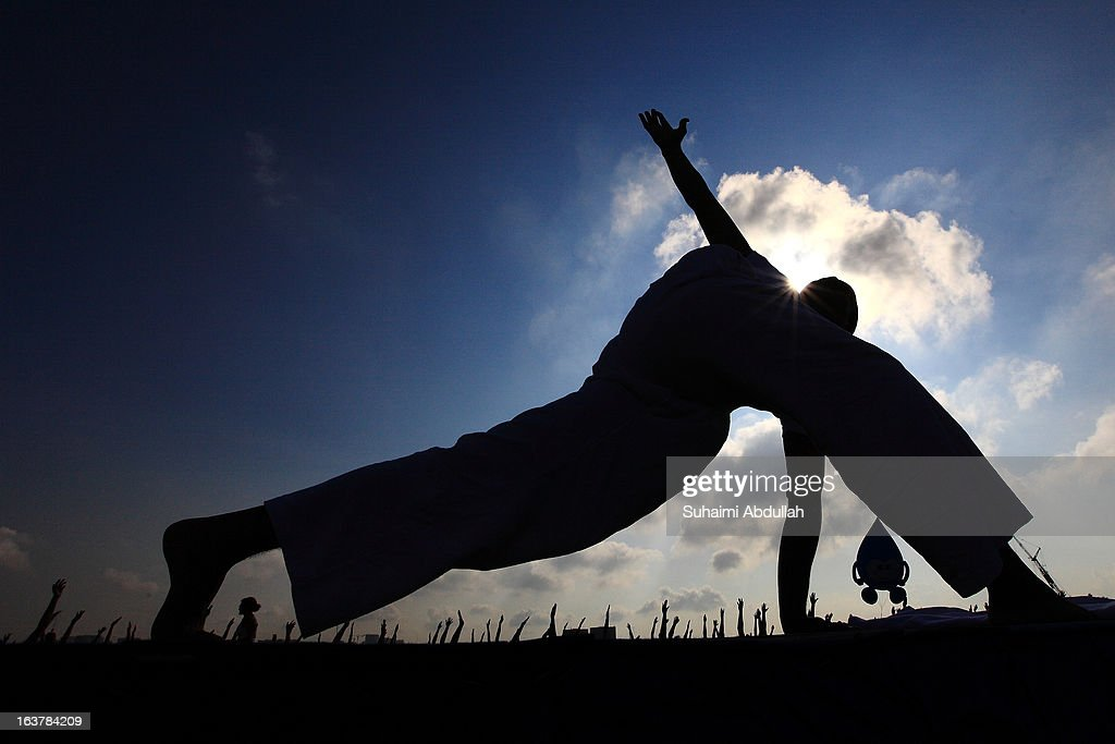A participant form up a yoga position during the mass yoga session on the green roof of Marina Barrage in celebration of the Singapore World Water Day on March 16, 2013 in Singapore. World Water Day is a global celebration of the importance of freshwater, and the crucial need for sensibile and sustainable management of water.
