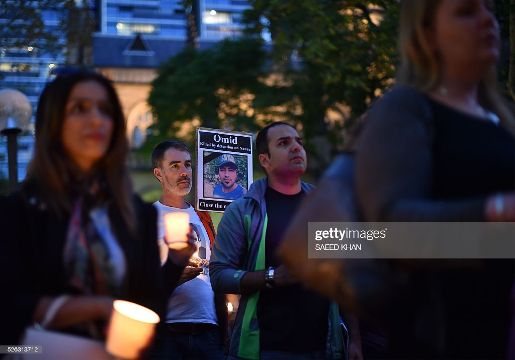 Participant hold candles during a vigil for an Iranian refugee, who died after setting himself on fire, in Sydney on April 30, 2016. The 23-year-old known as Omid set fire to himself on April 27, 2016 on the remote Pacific island where he had been sent by Australia, which refuses to resettle boat people even if found to be genuine refugees. / AFP / SAEED