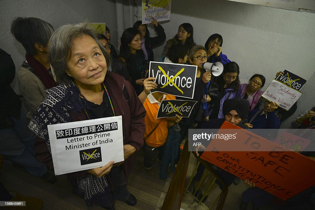 Participant hold placards as they wait in the stairwell after the lifts were stopped while on their way to the Indian consulate in Hong Kong on January 1, 2013 during an 'anti-violence towards women' march after the death of an Indian gang rape victim. The family of an Indian gang-rape victim said on December 31 they would not rest until her killers are hanged as police finalised their investigation before charges are laid against suspects this week. AFP PHOTO / Antony DICKSON