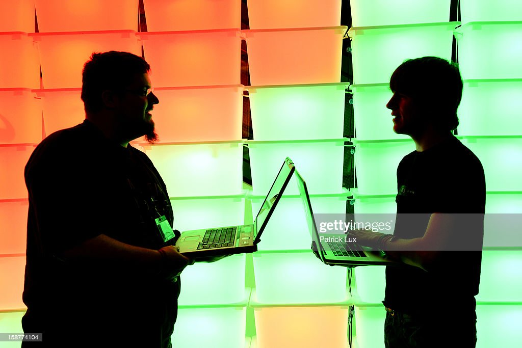 Participant hold their laptops in front of an illuminated wall at the annual Chaos Computer Club (CCC) computer hackers' congress, called 29C3, on December 28, 2012 in Hamburg, Germany. The 29th Chaos Communication Congress (29C3) attracts hundreds of participants worldwide annually to engage in workshops and lectures discussing the role of technology in society and its future.