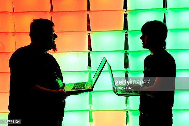 Participant hold their laptops in front of an illuminated wall at the annual Chaos Computer Club computer hackers' congress called 29C3 on December...