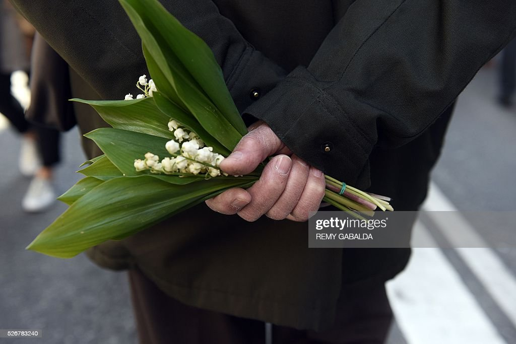 A participant holds a bouquet of lily of the valley during the traditional May Day demonstration in Toulouse, southern France, on May 1, 2016. / AFP / REMY
