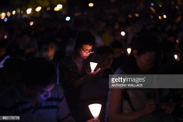 TOPSHOT A participant holds a candle as she and others attend a candlelight vigil at Hong Kong's Victoria Park on June 4 to mark the 28th anniversary...