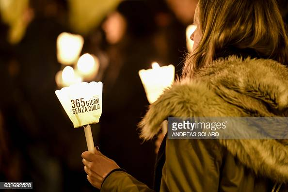 A participant holds a candle with the lettering '365 days without Giulio' as activists of human rights organization Amnesty International take part...