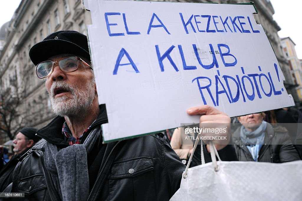 A participant holds a placard reading 'Away with your hands from the Klubradio' as employers of Hungary's opposition radio, the 'Klubradio' and their sympathizers attend a demonstration for the freedom of speech in Budapest on February 24, 2013. Hungarian court is ruling on March 5, on opposition Klubradio's fight against authorities for a new frequency.