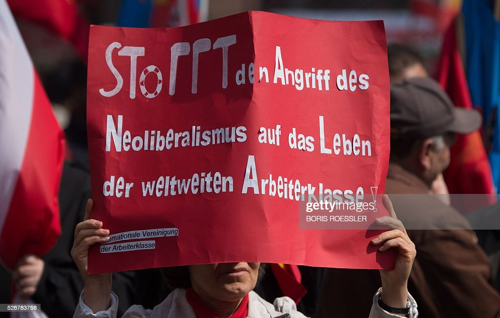 A participant holds a sign reading 'Stop the attack of the neoliberalism on the working class' life' during a May Day or International Workers' Day rally in Frankfurt am Main, central Germany, on May 1, 2016. / AFP / dpa / Boris Roessler / Germany OUT